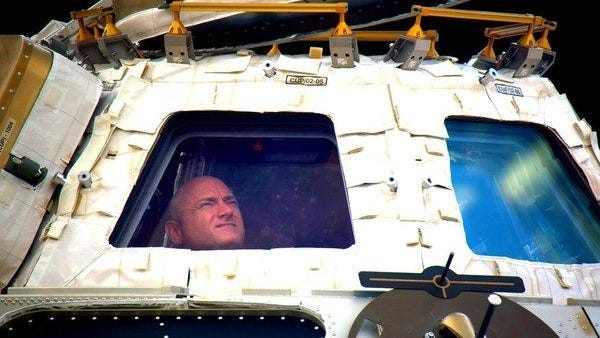 In this undated photo provided by NASA on Tuesday, March 1, 2016, astronaut Scott Kelly looks out the cupola of the International Space Station. Kelly closes the door Tuesday to an unprecedented year in space for NASA, flying back to the planet and loved ones he left behind last March. (NASA via AP)