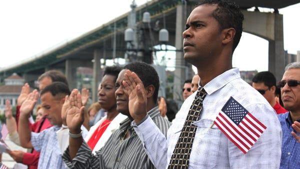 Novos cidadãos americanos fazem o Juramento de Fidelidade aos Estados Unidos durante uma cerimónia de naturalização realizada em Fall River.