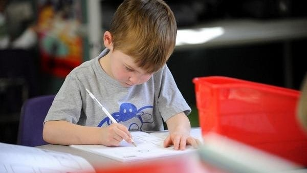 """In this 2014 file photo, pre-K student Lucas Evans, 3, works on writing lowercase """"a"""" at Knowledge Beginnings in Brookline."""