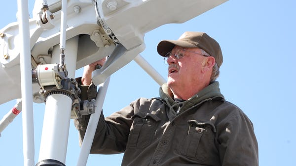 Ron Paye inspects the blades of a restored Huey helicopter from the Vietnam era. Paye, a Wisconsin native who flew helicopters in Vietnam, will fly a Huey in Sheboygan this week for a veterans' memorial event.