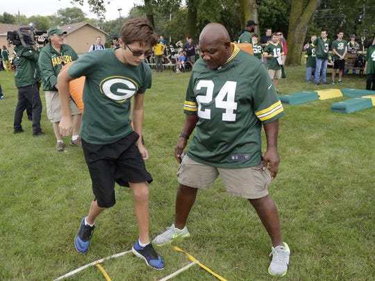 Packers alumni Johnnie Gray helps a student during the Green Bay Packers Youth Football Outreach Camp at Syble Hopp School in De Pere.