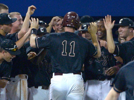 College of Charleston's Nick Pappas (11) is congratulated by teammates at the dugout after hitting a solo home run during the eighth inning of an NCAA college baseball regional tournament game against Long Beach State in Gainesville, Fla., Saturday, May 31, 2014. Charleston won 6-3. (AP Photo/Phelan M. Ebenhack)