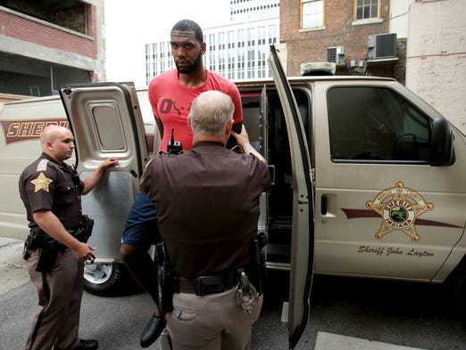 Greg Oden is escorted into the Marion County Community Corrections building, on Thursday, August 7, 2014, in Indianapolis. Oden was arrested for battery on his ex-girlfriend.