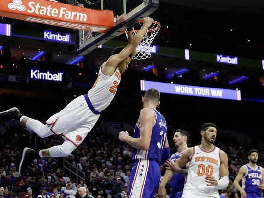 New York Knicks' Kevin Knox, left, hangs on the rim after a dunk against Philadelphia 76ers' Mike Muscala during the first half of an NBA basketball game, Wednesday, Dec. 19, 2018, in Philadelphia. (AP Photo/Matt Slocum)