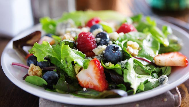 Leafy salads, such as this fresh berries and greens salad, are perfect for the summertime heat.
