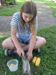 Maddie Wondra of Fond du Lac learns how to grind corn using elbow grease at the Galloway House & Village's summer enrichment sessions.