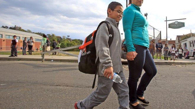 Carlene Pichardo walks with her son, Matthew, 8, a student at Cedar Place School in Yonkers, on Tuesday. A student at the school was diagnosed with enterovirus-D68.