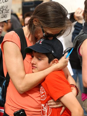 """Anastacia Andrade hugs her 9-year-old son Alejandro who joined with the March For Our Lives protesters who demand """"their lives and safety become a priority and that we end gun violence and mass shootings in our schools and communities"""" march at the Arizona State Capitol on Mar. 24, 2018 in Phoenix, Arizona."""