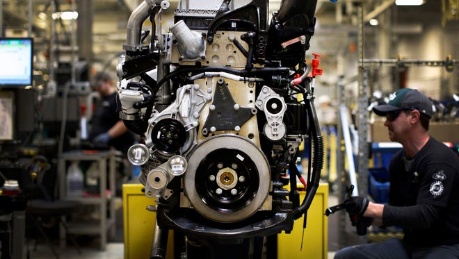 A truck engine sits on an assembly line as Ed Carbaugh prepares to install parts at a Volvo Trucks' manufacturing facility in Hagerstown, Md.,  in March 2014.