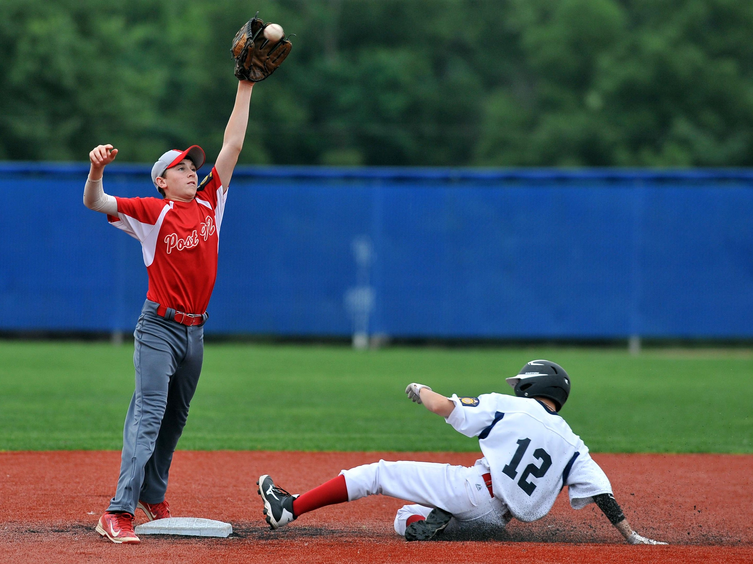 Utica Post 92 Juniors second baseman Dillion Carr snags a high throw as Lancaster Post 11's Tyler Lanning steals second base Wednesday night at Beavers Field during the state tournament. Post 92 won the game 9-7.