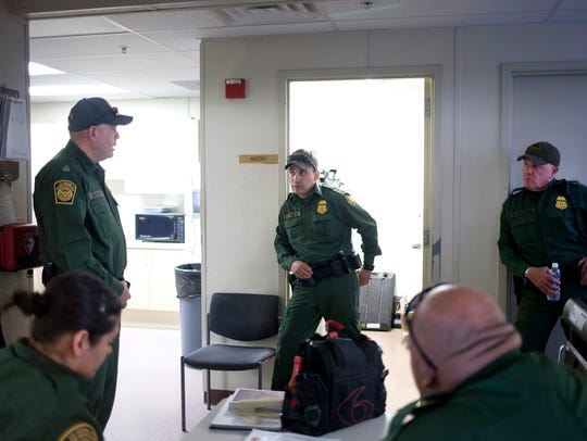 Jose Romero (left) and other Border Patrol agents talk