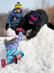 John Azpell helps Gabriela Gamez, 3, up to the top