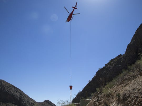 A helicopter drops water at the Waterman Mountain water catchment near Tucson.