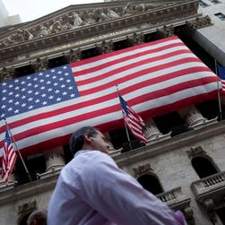 In this Monday, Aug. 8, 2011 file photo, a pedestrian walks past the New York Stock Exchange in New York.