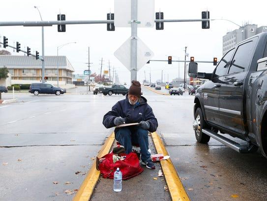 "Dennis Heiskill makes a new sign, writing ""Homeless"
