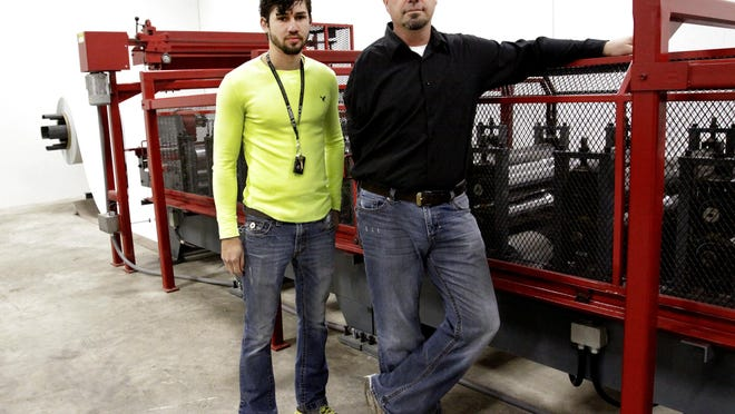 Yoder Metal co-owners Mark Nissley, right, and  son-in-law Steve Yoder stand next to a metal roller at their warehouse in this March 3, 2015 file photo. The Reno County Commission approved a conditional use permit on Tuesday allowing the business to construct another building and expand its local production of roll form metal.