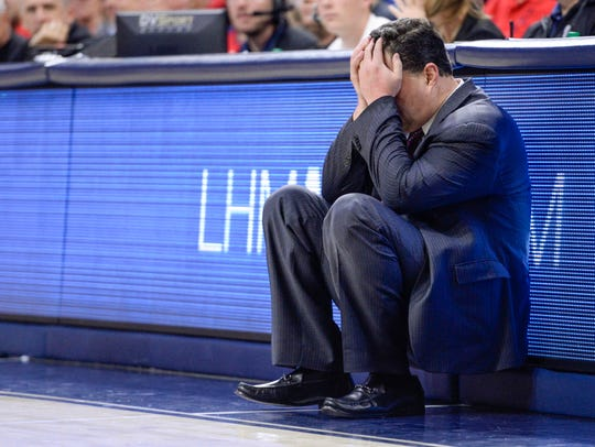 Arizona Wildcats head coach Sean Miller sits with his