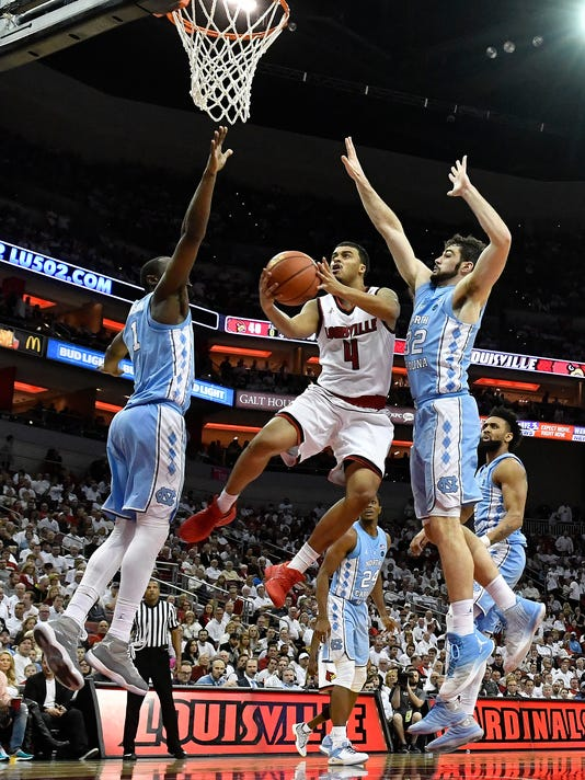 Louisville guard Quentin Snider (4) splits the defense of North Carolina forward Luke Maye (32) and forward Theo Pinson (1) as he attempts a layup during the second half of an NCAA college basketball game, Saturday, Feb. 17, 2018, in Louisville, Ky. (AP Photo/Timothy D. Easley)