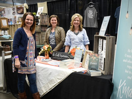 "Kendra Roehl, Julie Fisk and Kristin Demery stand at their conference display for their new book, ""The One Year Daily Acts of Kindness Devotional"" Friday, Oct. 13, at the River's Edge Convention Center in St. Cloud."