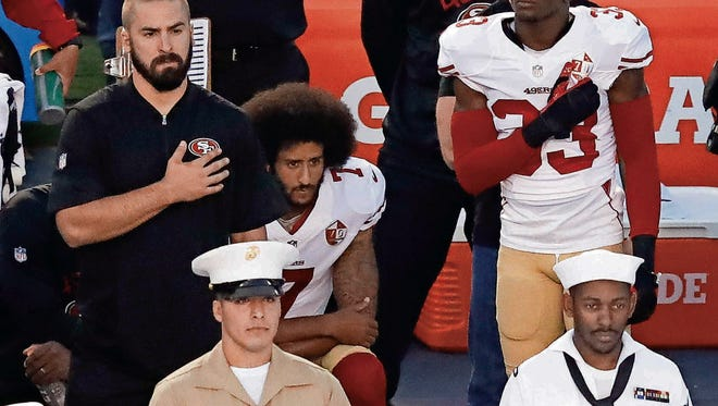 San Francisco 49ers quarterback Colin Kaepernick, middle, kneels during the national anthem before the team's NFL preseason football game against the San Diego Chargers.