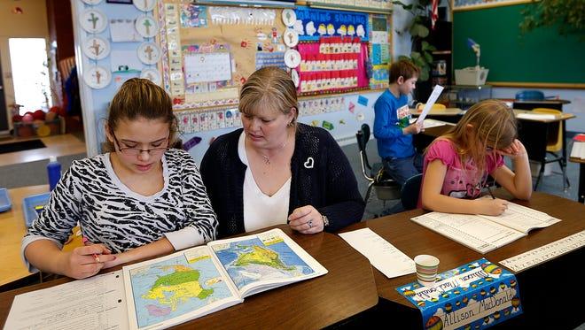 Benton Lake Elementary School teacher, Dawn Dawson helps students in her one-room school house. Dawson was recently named Montana's rural school teacher of the year.