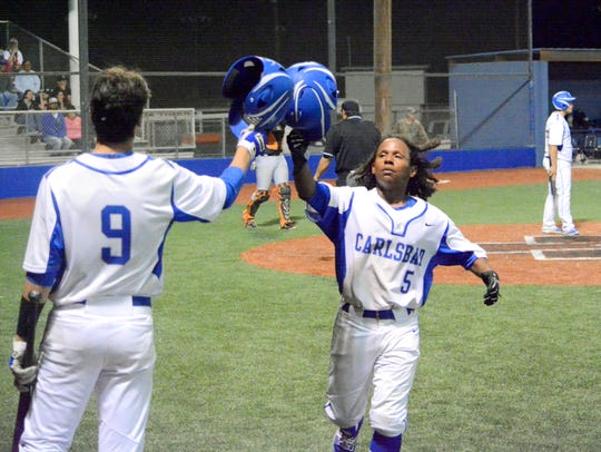 Carlsbad's Jonah Mathews (5) celebrates scoring a run