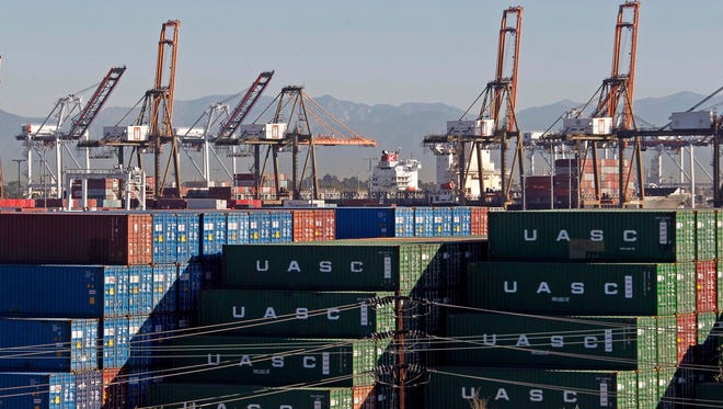 Cargo-loading cranes are upright and idle at the ports of Los Angeles and Long Beach on Feb. 12, 2015. A labor dispute is delaying loading and unloading at West Coast ports, where some automakers' key components arrive. Honda and Toyota have cut production in some factories for lack of parts.