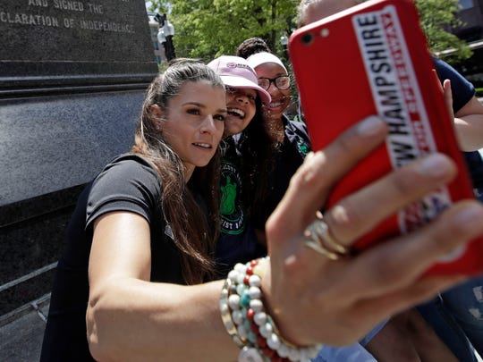 "NASCAR driver Danica Patrick, left, shoots selfies with students from the Warren-Prescott school at Faneuil Hall during a tour of historic sites, Wednesday, June 14, 2017, in Boston. Patrick says she ""had a moment"" when she lost her temper at a booing fan after qualifying for last week's NASCAR race."