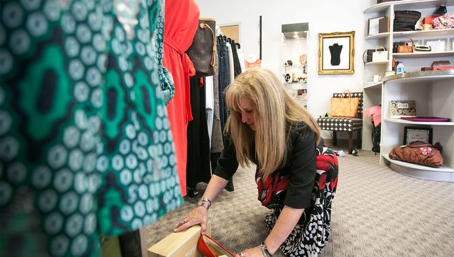 Fashion Cents Consign & Redesign owner Linda Heindel, rearranges Michael Kors shoes Friday, April 1, 2016, in preparation for Consignment Week, which runs April 3-9. Amanda J. Cain photo
