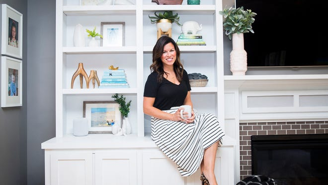 Interior designer Kristen Suding poses in front of a bookshelf in her home.