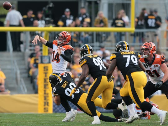 Cincinnati Bengals quarterback Andy Dalton (14) throws the ball out of bounds as he's pressured by Pittsburgh Steelers outside linebacker T.J. Watt (90) in the second quarter during the Week 7 NFL game between the Cincinnati Bengals and the Pittsburgh Steelers, Sunday, Oct. 22, 2017,  at Heinz Field in Pittsburgh.