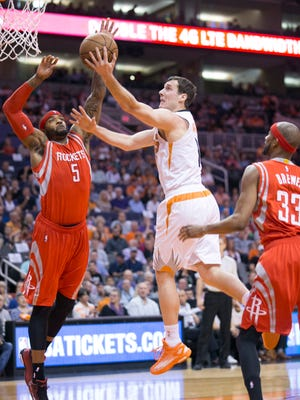 Suns guard Goran Dragic puts up a shot as the Rockets Josh Smith (5) defends during the first quarter of the NBA game at the US Airways Center in Phoenix on Tuesday, February 10, 2015.