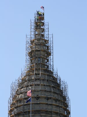"""In this photo provided by Dan Brocklehurst, Capitol facilities director, crews from the Taylor-based Brand Energy & Infrastructure Services celebrate the """"topping-out"""" of the scaffolding around the Capitol dome. The scaffolding will support a restoration of the dome's exterior throughout this summer."""