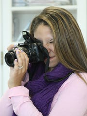 Jasmine Hayslett's snapping a photo while working on the yearbook at Fort Defiance High School.
