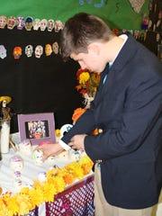 Edward Porras placed a sugar skull on a display.
