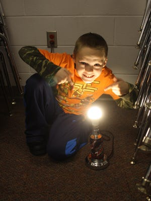 STEAM Academy student J.J. Hunt shows off his working lamp he made out of a lamp kit and recycled soda can.