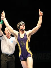 Amherst native and UW-Stevens Point junior Logan Hermsen has his hand raised in victory after winning the NCAA Division III 165-pound national championship in Cedar Rapids, Iowa on Saturday night.