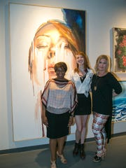 "(left to right) President of Idyllwild Arts Foundation,  Pamela Jordan, Idyllwild Arts Academy student Audrey whose painting  ""Neurotic Energy"" is seen in the background, and Melissa Morgan, Owner  of Melissa Morgan Fine Art."