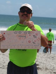 Clayton Guage, 47, an autistic surfer, shows off his