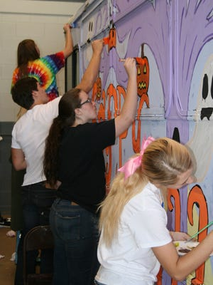 Clarksville Academy art students put the finishing touches on their Spooky Special paint job at the CTS maintenance garage on Friday.