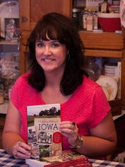 "Author Darcy Maulsby holds a copy of her book, ""A Culinary History of Iowa."""