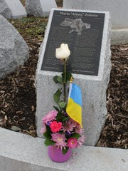 A single white rose and Ukrainian flag was placed beside a plaque dedicated to American Civic Association shooting victim Maria Zobniw on April 3, 2017.