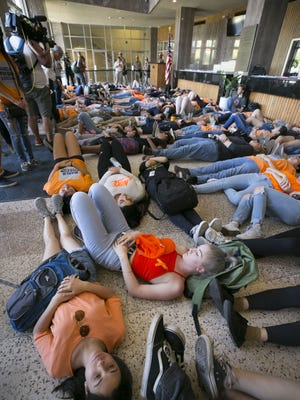 """High school students participate in a """"die-in"""" in the lobby of the Arizona Senate building during a protest organized by the March for Our Lives movement  at the Arizona Capitol in Phoenix on April 20, 2018."""