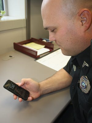 Florence Police Department Corp. Ryan Thoman tests out the department's new mobile app.