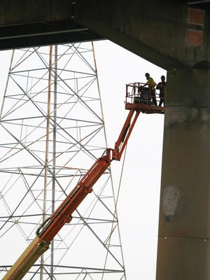 Work continues on the I-495 bridge near one of the leaning supports. Crews have been hauling away a 55,000-ton mound of dirt near the span.