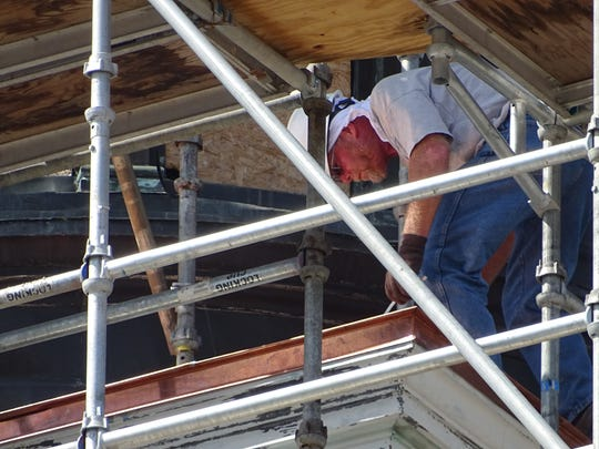 A construction worker negotiates the scaffolding surrounding