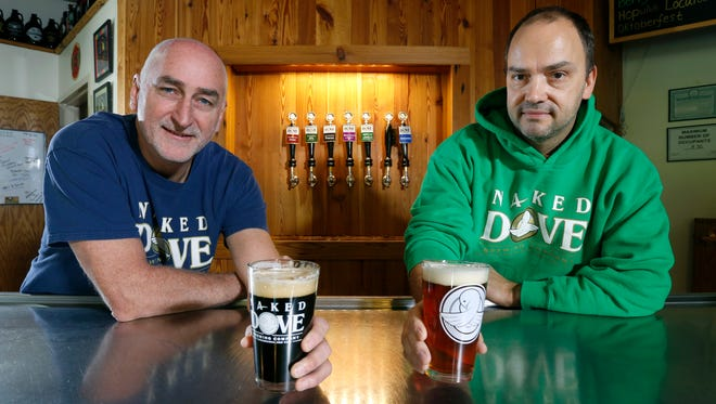 Naked Dove Brewing Co. owners Don Cotter, holding a 45 Fathoms Porter, and Dave Schlosser with a Hopulus Localus in Canandaigua.