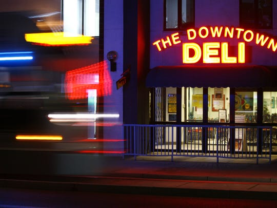 A light rail train passes The Downtown Deli on July