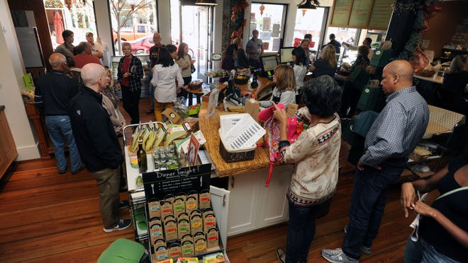 Customers browse at The Bodacious Olive, at the Block of Palafox Street south of Zarragossa and north of Main Street, on Small Business Saturday in 2016.