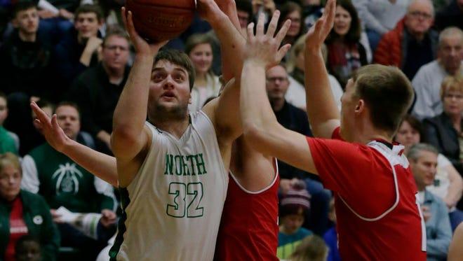 Oshkosh North's Matt Hickey looks to shoot over Kimberly's defense.